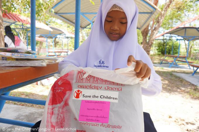 Sikin excitedly opens her distribution kits, including educational materials, school bags, and uniforms